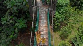 Tiro a?reo de una mujer joven y de su peque?o hijo que caminan en un puente del suspention sobre las selvas Vacaciones en las zon almacen de metraje de vídeo