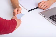 Tiro sem cara do homem de negócios que dá o cartão ao sócio, sentando-se na mesa branca com laptop e caderno, povos foto de stock