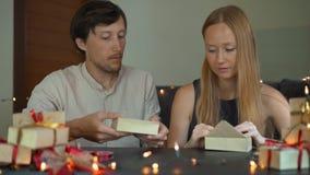 Tiro Slowmotion de presentes do envoltório de uma jovem mulher e do pai e da mãe do homem Presentes envolvidos no papel do ofício vídeos de arquivo