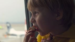 Tiro Slowmotion de um menino novo em um revestimento amarelo que come uma cookie que sittting na frente de uma janela grande em u vídeos de arquivo