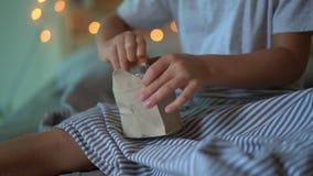 Tiro Slowmotion de um rapaz pequeno que abre um presente de um calendário do advento que esteja pendurando em uma cama que seja i video estoque