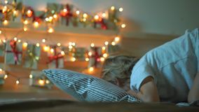 Tiro Slowmotion de um rapaz pequeno que olha um calendário do advento que pendura em uma cama para iluminar com luzes de Natal co filme