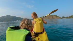 Tiro Slowmotion de uma família nova que kayaking em um mar tropical e que tem o divertimento que olha o recife de corais e peixes filme