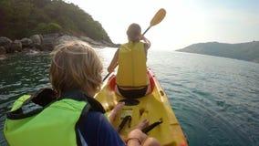 Tiro Slowmotion de uma família nova que kayaking em um mar tropical e que tem o divertimento que olha o recife de corais e peixes video estoque