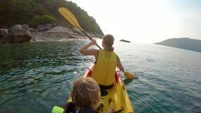 Tiro Slowmotion de uma família nova que kayaking em um mar tropical e que tem o divertimento que olha o recife de corais e peixes vídeos de arquivo