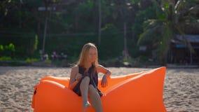 Tiro Slowmotion de uma jovem mulher em uma praia tropical que senta-se em um sofá inflável Conceito das f?rias de ver?o vídeos de arquivo