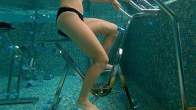 Tiro Slowmotion de uma jovem mulher que faz exercícios em uma escada rolante subaquática da bicicleta e do aqua de exercício do a filme