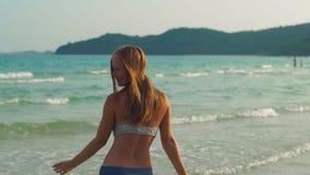 Tiro Slowmotion de uma mulher beatyful nova que tem o divertimento em uma praia e no mar video estoque
