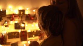 Tiro Slowmotion do close up de uma mãe e de seu olhar pequeno do filho em um calendário do advento que pendura em uma cama para i vídeos de arquivo