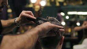 Tiro Slowmotion: A ideia do close up do ` s do barbeiro entrega a execução de um corte de cabelo com as tesouras e o penteado do  video estoque