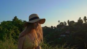 Tiro slowmotion super de uma jovem mulher em um vestido amarelo que anda durante o por do sol na caminhada ou no pintor do cume d vídeos de arquivo