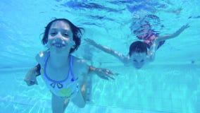 Tiro subacuático de dos niños que se zambullen en una piscina almacen de metraje de vídeo