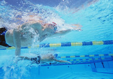 Tiro subacuático de tres atletas de sexo masculino en la competencia de la natación Fotografía de archivo libre de regalías