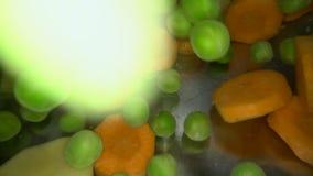 Tiro subaquático dos legumes frescos que estão sendo deixados cair na água Cozinhando a sopa vegetal no potenciômetro do metal: e filme