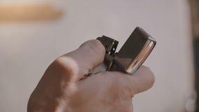 Tiro super do close-up do isqueiro metálico de prata de abertura do cigarro do vintage da mão masculina, tentando acender e obter video estoque