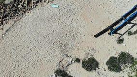 Tiro superior aéreo sobre la playa arenosa con las botellas inútiles plásticas de la basura Playa rocosa arenosa sucia con las bo almacen de video