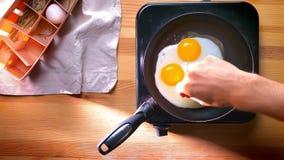 Tiro superior, adicionando o sal aos ovos em casa quase cozinhados na bandeja, hábitos comendo saudáveis internos, alimento simpl video estoque