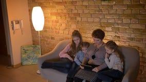 Tiro superior da mãe caucasiano e três das filhas que olham na tabuleta com atenção e interesse na casa confortável vídeos de arquivo