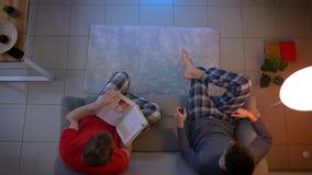 Tiro superior de amigos en la ropa de noche que cambia programas de la TV con el control remoto y que lee un libro en la sala de  almacen de metraje de vídeo