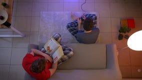 Tiro superior de amigos en la ropa de noche que juega el videojuego con la palanca de mando y que lee un libro en la sala de esta almacen de metraje de vídeo