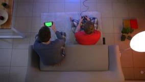 Tiro superior de amigos en la ropa de noche que juega el videojuego con la palanca de mando y que mira en smartphone en la sala d almacen de video