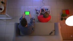 Tiro superior de amigos en la ropa de noche que juega el videojuego con la palanca de mando y la tableta en la sala de estar almacen de metraje de vídeo