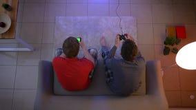 Tiro superior de amigos en la ropa de noche que juega el videojuego usando la palanca de mando y que trabaja con smartphone en la almacen de video