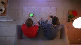 Tiro superior de amigos en la ropa de noche que reacciona emocionalmente en juego y que trabaja con smartphone en la sala de esta almacen de metraje de vídeo