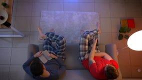 Tiro superior de amigos en película de observación de la ropa de noche con el control remoto y la lectura de un libro atento en l almacen de metraje de vídeo
