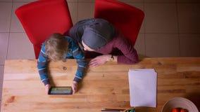 Tiro superior de desenhos animados de observação do menino pequeno na tabuleta e em sua mãe muçulmana no hijab observando sua ati filme