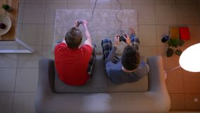 Tiro superior de dos amigos en la ropa de noche que juega el videojuego usando la palanca de mando y que reacciona emocionalmente almacen de video