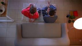 Tiro superior de dos individuos jovenes en la ropa de noche que juega el videojuego activamente usando la palanca de mando que se almacen de video