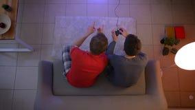 Tiro superior de dos individuos jovenes en la ropa de noche que juega el videojuego y que comunica con gestos activos en la sala  almacen de video