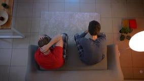 Tiro superior de dos individuos jovenes en ropa de noche que ven la TV y que reaccionan emocionalmente para contentar en la sala  metrajes