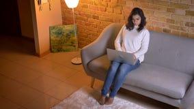Tiro superior de la empresaria morena caucásica atenta que sienta en el sofá con los cambios del ordenador portátil la posición d metrajes