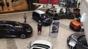 Tiro superior de la gente que hace compras y que mira el coche de la exhibición almacen de metraje de vídeo