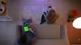 Tiro superior de la muchacha en la ropa de noche que juega el videojuego con la palanca de mando y al individuo que trabaja con l almacen de metraje de vídeo