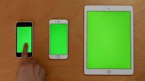 Tiro superior de los teléfonos y del ipad del tacto de la mano en la pantalla verde
