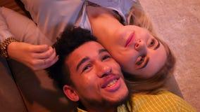 Tiro superior de pares del individuo africano y de la muchacha caucásica que mienten en el sofá y que hablan con uno a alegre en  metrajes