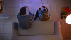 Tiro superior de pares jovenes en la ropa de noche que juega el videojuego con las palancas de mando y que gana en la sala de est almacen de video