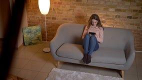 Tiro superior del adolescente rubio joven que se sienta en el sofá y que mira atento en la tableta en atmósfera casera acogedora almacen de video