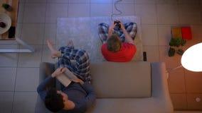 Tiro superior del individuo en la ropa de noche roja que juega el videojuego con la palanca de mando y de otro que leen un libro  metrajes