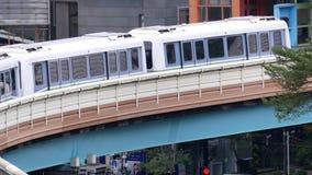 Tiro superior del MRT que pasa al lado del edificio durante hora punta