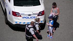Tiro superior del oficial de policía que abraza con los niños