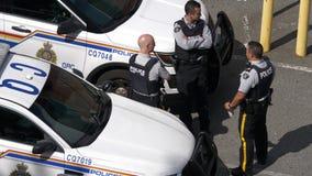 Tiro superior del oficial de policía que charla con el colega en el estacionamiento