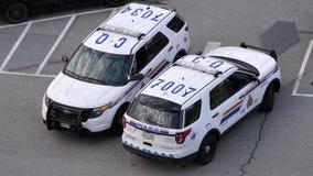 Tiro superior del oficial de policía que charla con la gente al lado del coche policía