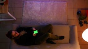 Tiro superior do close up do adolescente f?mea bonito que olha a tev? usando o telefone com tela verde ao encontrar-se no sof? filme