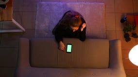 Tiro superior do close up do adolescente fêmea bonito que olha a tevê usando o telefone com tela verde ao sentar-se no assoalho filme