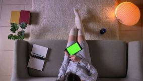 Tiro superior do close up da consultação fêmea atrativa nova na tabuleta com a tela verde do croma que senta-se no sofá dentro vídeos de arquivo
