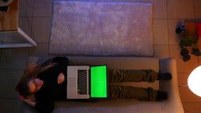 Tiro superior do close up da datilografia consideravelmente f?mea no port?til com tela verde ao encontrar-se no sof? dentro em um video estoque